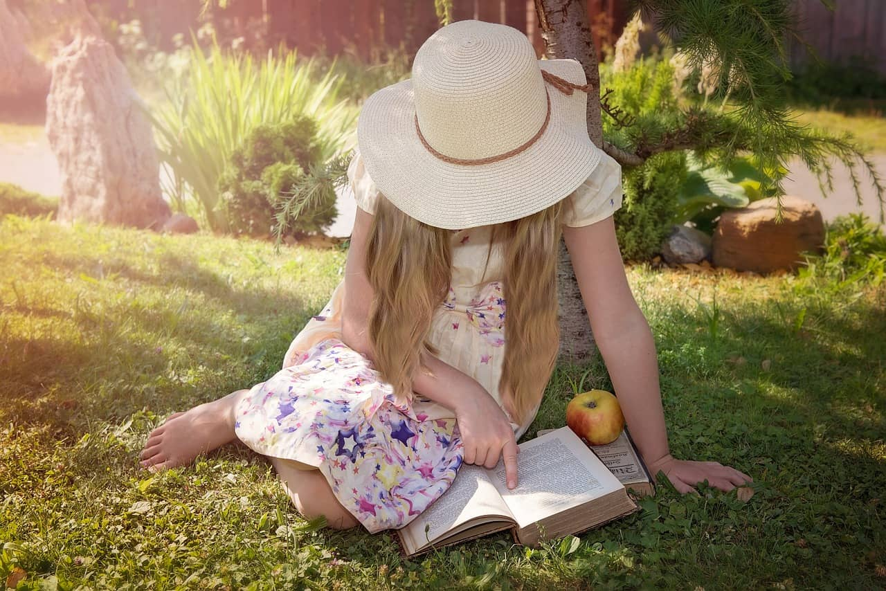 girl with hat sitting in sun reading a book